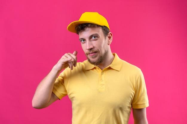 Entregador de camisa pólo amarela e boné fazendo gesto de me ligar parecendo confiante sorrindo amigável na rosa