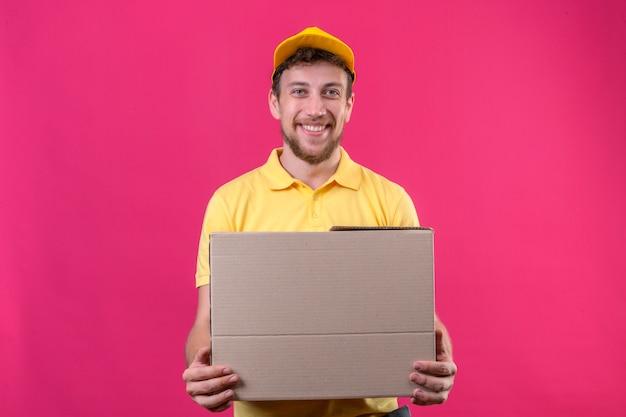 Entregador de camisa pólo amarela e boné segurando a embalagem da caixa, parecendo confiante, sorrindo alegremente em pé no rosa isolado