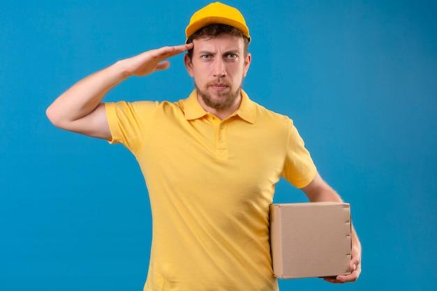 Entregador de camisa pólo amarela e boné segurando a embalagem da caixa saudando com a mão parecendo confiante em pé no azul isolado