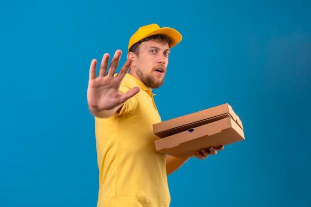 Entregador de camisa pólo amarela e boné segurando caixas de pizza em pé com a mão aberta fazendo sinal de pare o gesto de defesa parecendo assustado no azul isolado