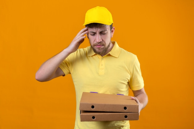 Entregador de camisa pólo amarela e boné segurando caixas de pizza em pé com a mão na cabeça por engano, lembre-se do erro, esqueci o conceito de memória ruim em laranja isolada