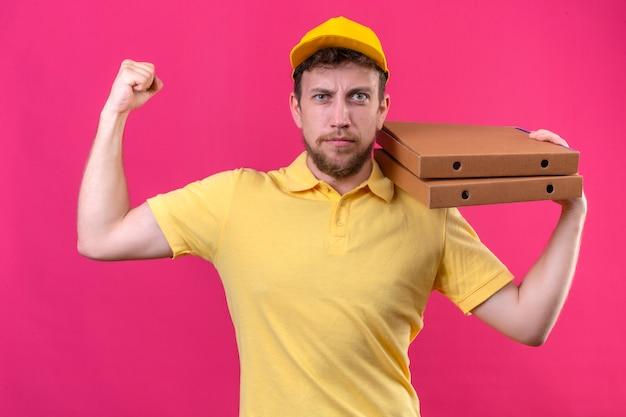 Entregador de camisa pólo amarela e boné segurando caixas de pizza no ombro mostrando bíceps como um vencedor em pé no rosa isolado