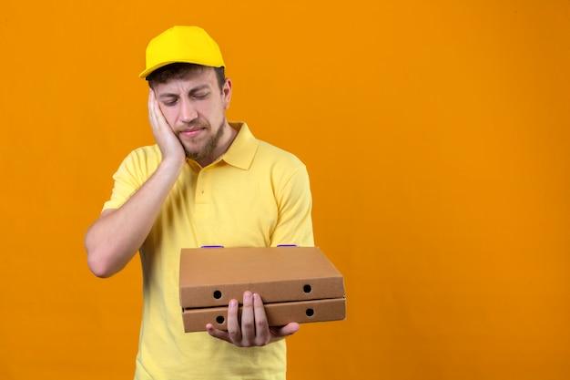 Entregador de camisa pólo amarela e boné segurando caixas de pizza parecendo mal em pé com a mão na bochecha sofrendo de dor de dente na laranja