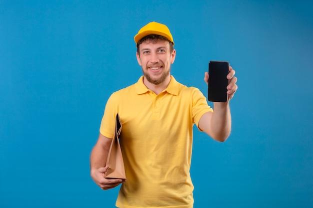 Entregador de camisa pólo amarela e boné segurando um pacote de papel e mostrando o smartphone sorrindo amigável com uma cara feliz em pé no azul