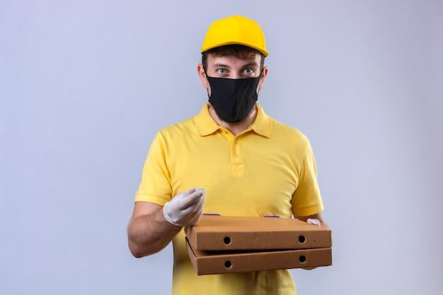 Entregador de camisa pólo amarela e boné usando máscara protetora preta com sorriso no rosto fazendo gesto de dinheiro com a mão em pé no branco