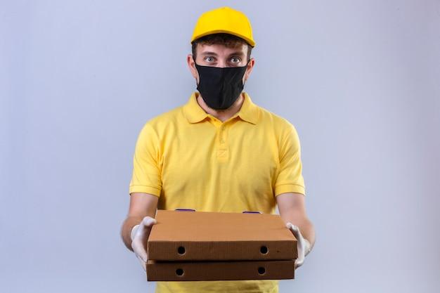 Entregador de camisa pólo amarela e boné usando máscara protetora preta segurando caixas de pizza com cara séria de pé no branco