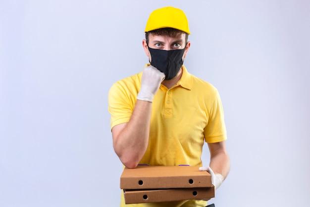 Entregador de camisa pólo amarela e boné usando máscara protetora preta segurando caixas de pizza esperando com a mão no queixo em branco isolado