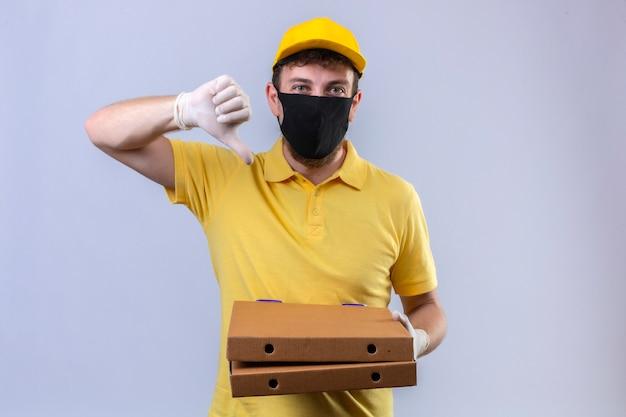 Entregador de camisa pólo amarela e boné usando máscara protetora preta segurando caixas de pizza mostrando polegares para baixo em pé no branco isolado