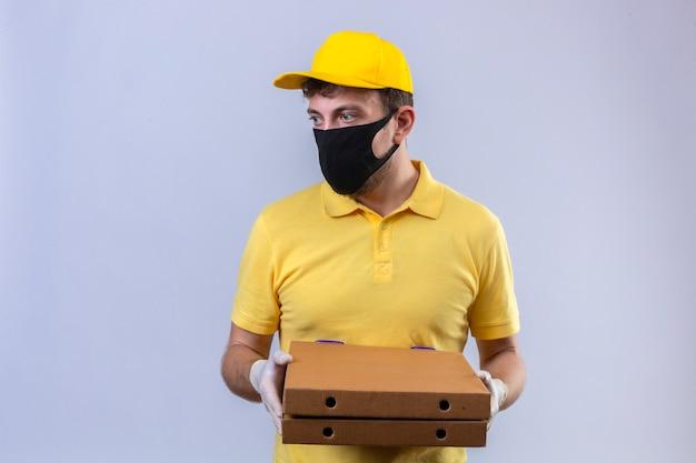 Entregador de camisa pólo amarela e boné usando máscara protetora preta segurando caixas de pizza olhando para o lado com uma cara séria parada no branco