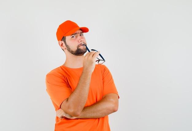 Entregador de camiseta laranja, boné mordendo os óculos e parecendo irresoluto, vista frontal.