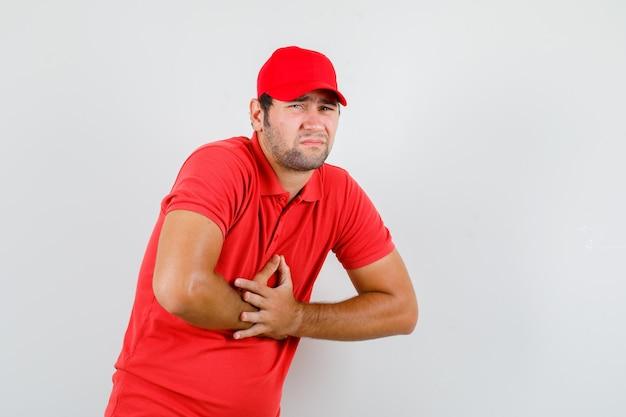 Entregador de camiseta vermelha, boné sofrendo de dores de estômago