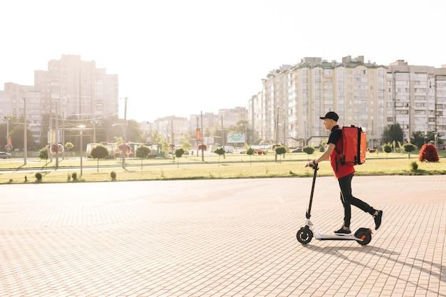 Entregador de comida asiática com mochila térmica vermelha andando na rua em uma scooter elétrica