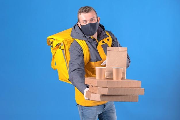 Entregador de comida com máscara médica e jaqueta amarela