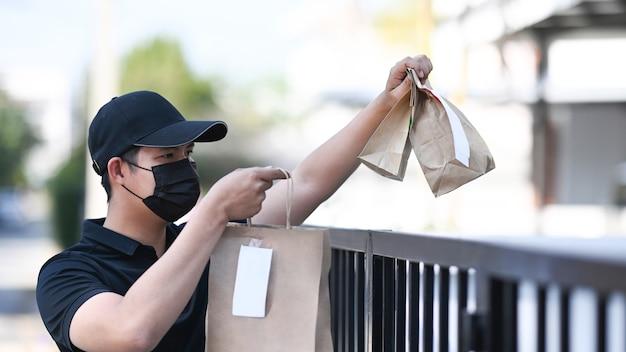 Entregador de comida com máscara protetora passa saco de papel com comida para o cliente na porta