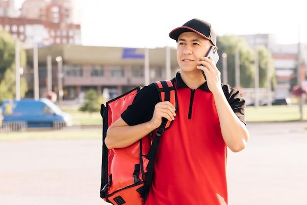 Entregador de comida com mochila vermelha entrega pedidos mensageiro masculino com caixa de caixa de comida isotérmica chega ...