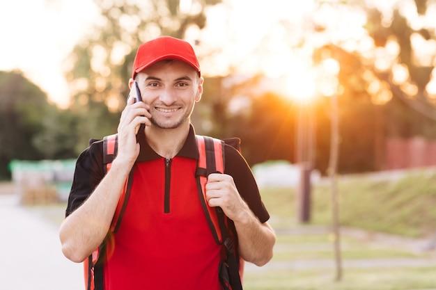 Entregador de comida com mochila vermelha entrega pedidos mensageiro masculino com caixa de comida isotérmica