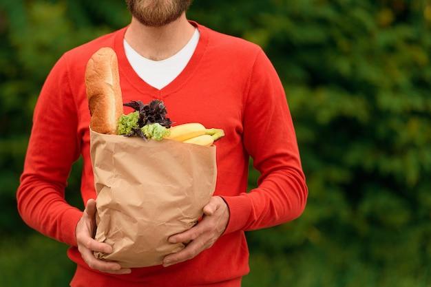 Entregador de comida com uniforme vermelho e sacola ecológica de papel segurando mantimentos