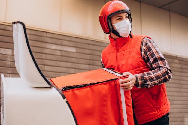 Entregador de comida dirigindo scooter com caixa com comida e usando máscara