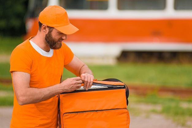 Entregador de comida em uniforme laranja abre uma sacola de entrega de comida.