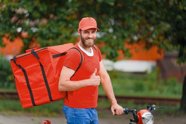 Entregador de comida em uniforme vermelho com sacola de entrega de comida nas costas, sorrindo e aparecendo o polegar.