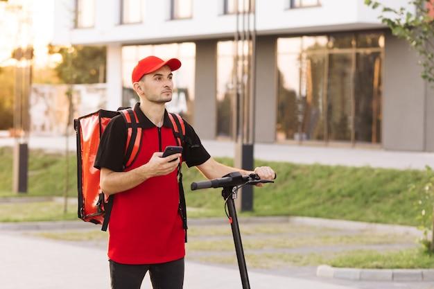 Entregador de comida masculino com mochila térmica vermelha caminha pela rua com scooter elétrico usa fone