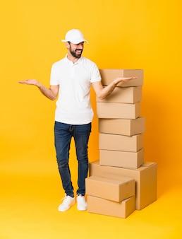 Entregador de comprimento total entre caixas ao longo da parede amarela isolada, segurando copyspace com as duas mãos