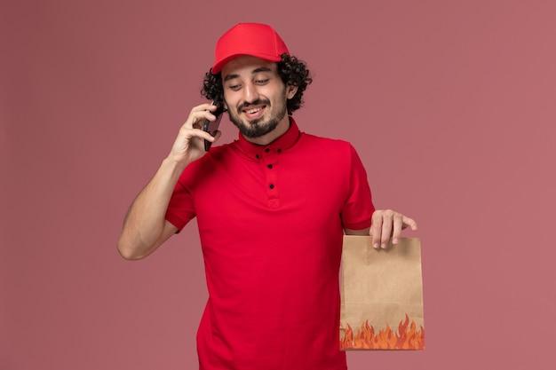 Entregador de correio masculino de camisa vermelha e capa, vista frontal, segurando um pacote de comida, falando ao telefone na parede rosa serviço de entrega de trabalho de funcionário