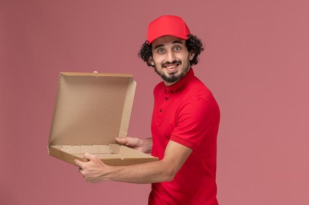 Entregador de correio masculino de camisa vermelha e capa, vista frontal, segurando uma caixa de comida vazia na parede rosa trabalhador de funcionário de empresa de entrega de serviço
