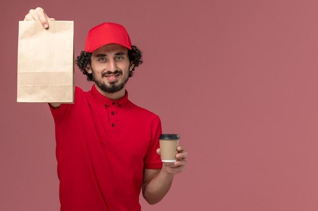 Entregador de correio masculino de camisa vermelha e capa, vista frontal, segurando uma xícara de café marrom e um pacote de comida na parede rosa claro serviço de entrega de trabalho de funcionário