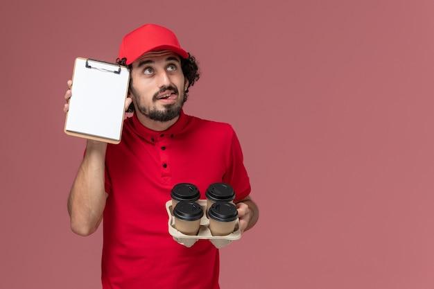 Entregador de correio masculino de camisa vermelha e capa, vista frontal, segurando xícaras de café marrons com um pequeno bloco de notas pensando no funcionário de entrega de serviço de parede rosa