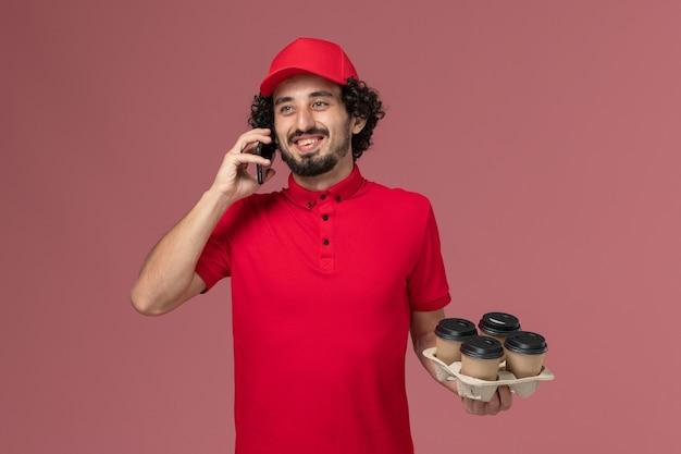 Entregador de correio masculino de camisa vermelha e capa, vista frontal, segurando xícaras de café marrons, junto com o telefone falando na parede rosa.