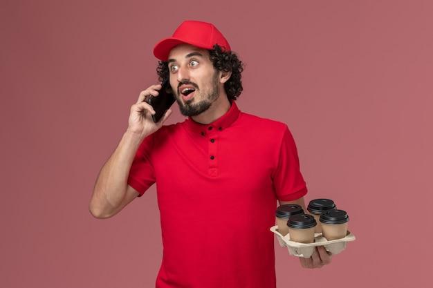 Entregador de correio masculino de camisa vermelha e capa, vista frontal, segurando xícaras de café marrons junto com o telefone na parede rosa trabalho de funcionário de entrega de serviço