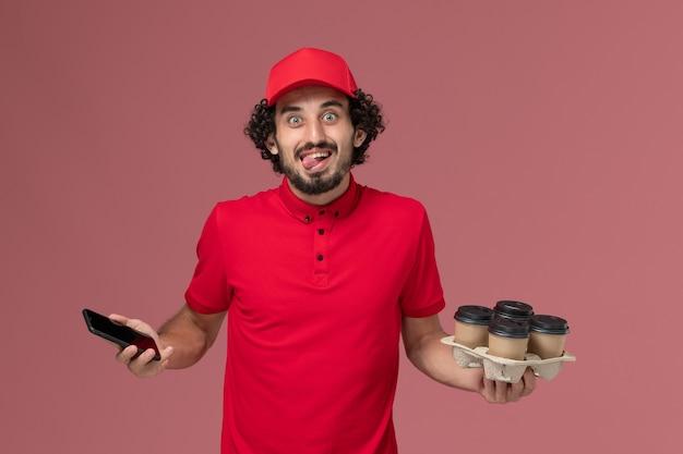 Entregador de correio masculino de camisa vermelha e capa, vista frontal, segurando xícaras de café marrons junto com o telefone na parede rosa.