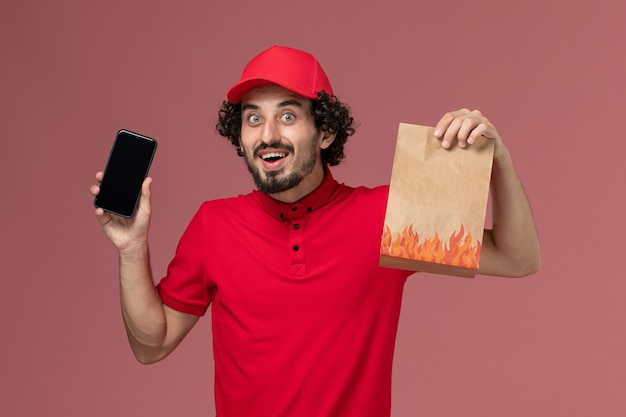 Entregador de correio masculino de vista frontal de camisa vermelha e capa segurando um pacote de comida e smartphone no funcionário de entrega de serviço de parede rosa