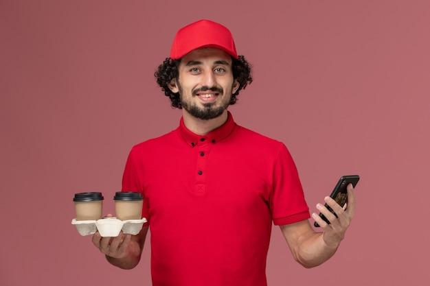 Entregador de correio masculino de vista frontal de camisa vermelha e capa segurando xícaras de café marrons e telefone na parede rosa serviço de entrega empregado trabalho masculino trabalhador