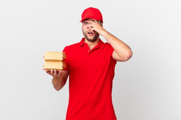 Entregador de hambúrguer parecendo chocado, assustado ou apavorado, cobrindo o rosto com a mão