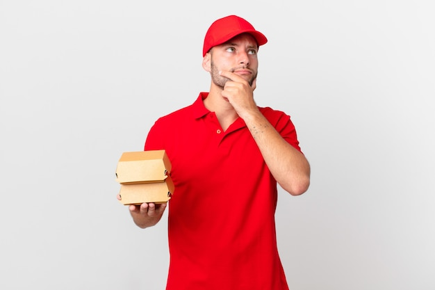Entregador de hambúrguer pensando, sentindo-se duvidoso e confuso