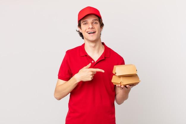 Entregador de hambúrguer sorrindo alegremente, feliz e apontando para o lado