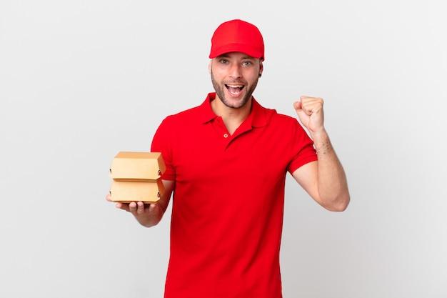 Entregador de hambúrgueres chocado, rindo e comemorando o sucesso