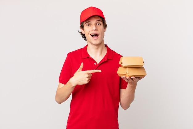 Entregador de hambúrgueres parecendo animado e surpreso apontando para o lado