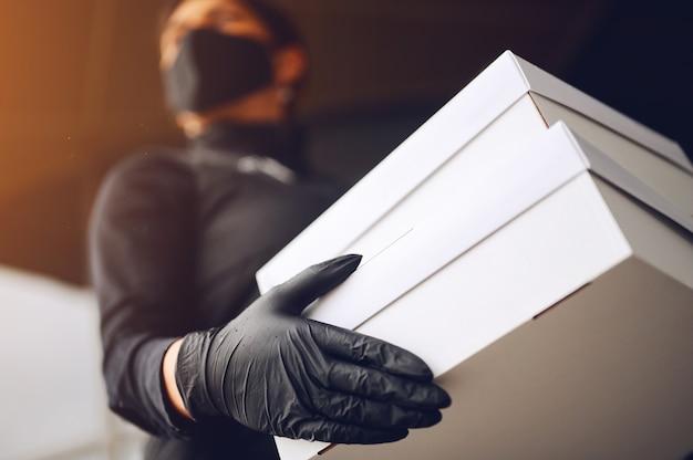 Entregador de máscara facial e luvas segurando a caixa de papelão branca ao ar livre