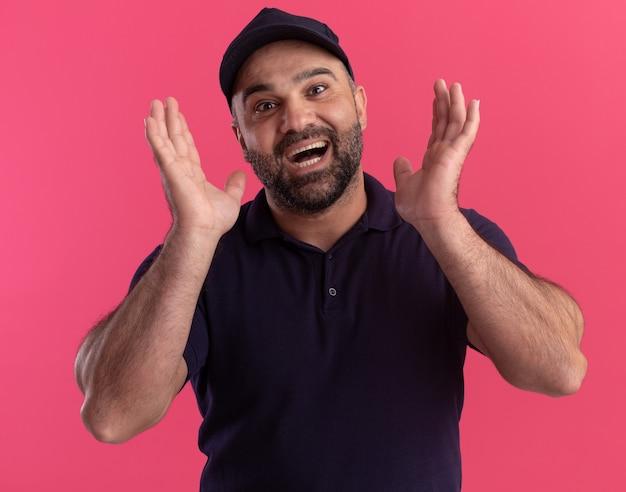 Entregador de meia-idade alegre de uniforme e boné de mãos dadas em torno do rosto isolado na parede rosa