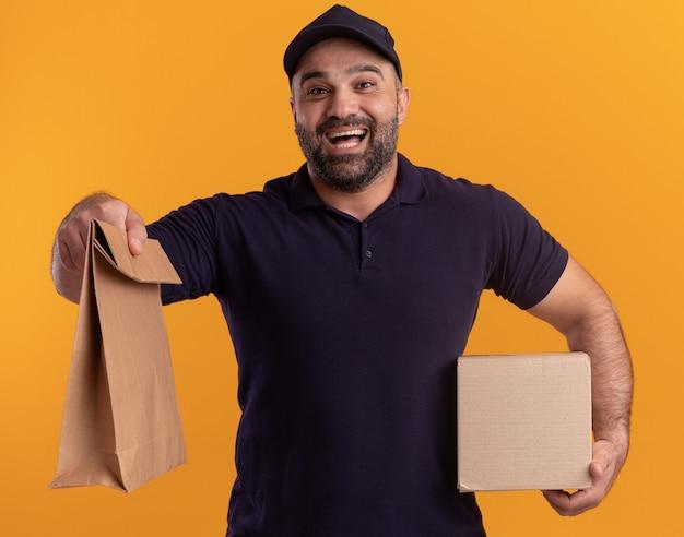 Entregador de meia-idade alegre de uniforme e boné segurando uma caixa e segurando um pacote de comida de papel isolado na parede amarela