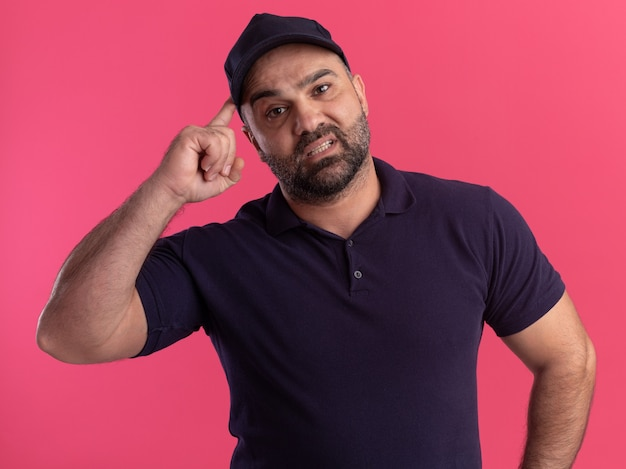 Entregador de meia-idade arrependido de uniforme e boné colocando o dedo na têmpora isolado em parede rosa