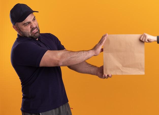 Entregador de meia-idade insatisfeito, de uniforme e boné, dando um pacote de comida de papel para o cliente isolado na parede amarela