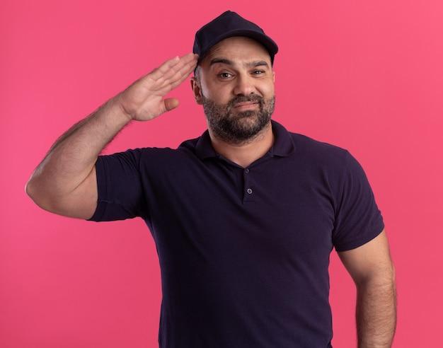 Entregador de meia-idade satisfeito, de uniforme e boné, mostrando gesto de saudação isolado na parede rosa