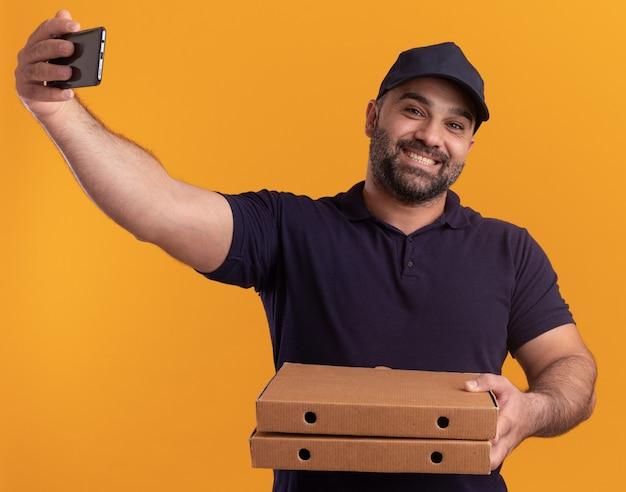 Entregador de meia-idade sorridente com uniforme e boné segurando caixas de pizza e tirando uma selfie isolada na parede amarela