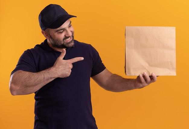 Entregador de meia-idade sorridente com uniforme e boné segurando e apontando para um pacote de comida de papel isolado na parede amarela