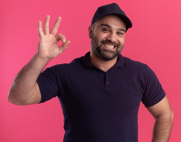 Entregador de meia-idade sorridente, de uniforme e boné, mostrando um gesto de aprovação isolado na parede rosa