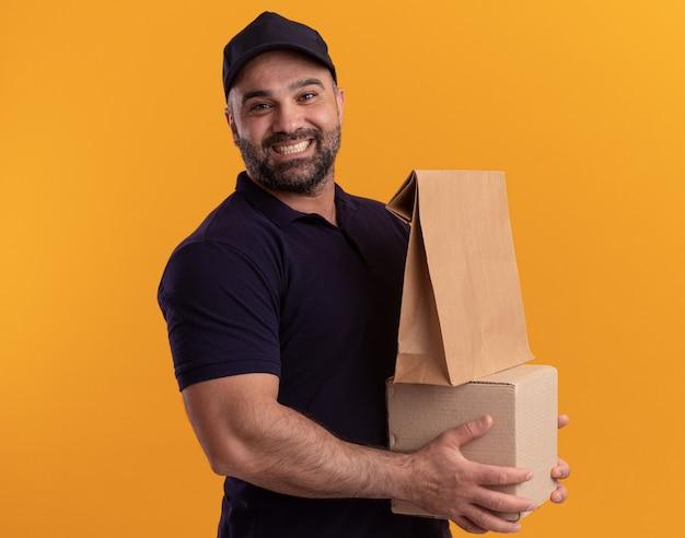 Entregador de meia-idade sorridente de uniforme e boné segurando uma caixa com um pacote de comida de papel isolado na parede amarela